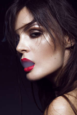 Beautiful sexy brunette girl with bright makeup, red lips, smoking with smoke from mouth. beauty face. Photos shot in the studio on a black background.