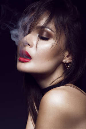 Beautiful brunette girl with bright makeup, red lips, smoking with smoke from mouth. beauty face. Photos shot in the studio on a black background.