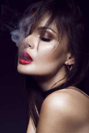 Hermosa chica atractiva morena con maquillaje brillante, labios rojos, fumando de humo por la boca. belleza de la cara. Las fotos tomadas en el estudio sobre un fondo negro.