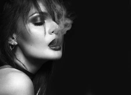 美しいセクシーなブルネットの少女明るい化粧、赤い唇、口から煙と喫煙します。美容顔。黒と白。黒の背景にスタジオで撮影した写真。