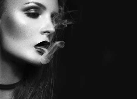 black girl smoking: Beautiful sexy brunette girl with bright makeup, red lips, smoking with smoke from mouth. beauty face. Black and white. Photos shot in the studio on a black background.