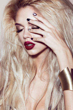 Beautiful sexy blonde girl with sensual lips, fashion hair, black nails. Beauty face. Picture taken in the studio