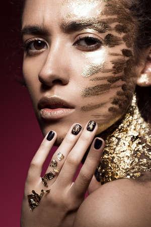 fille Beautyful avec des paillettes d'or sur son visage face.Art image de beauté. Photo prise dans le studio.