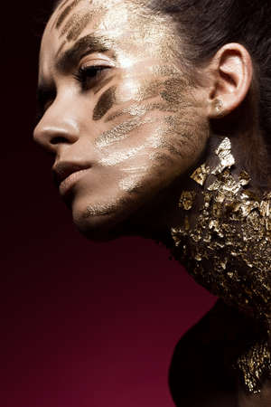 Beautyful girl with gold glitter on her face.Art image beauty face. Picture taken in the studio. Stok Fotoğraf