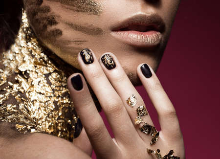 bodyart: Beautyful girl with gold glitter on her face.Art image beauty face. Picture taken in the studio. Stock Photo