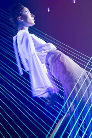 Fashion model beautiful girl in fashionable clothes in ultraviolet light, showing different poses. Beauty body and face. Photos shot in studio Stock Photo