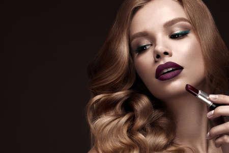 カール、暗い唇、手で口紅を配したハリウッドに金髪の美しい。美容顔と髪。スタジオでの撮影