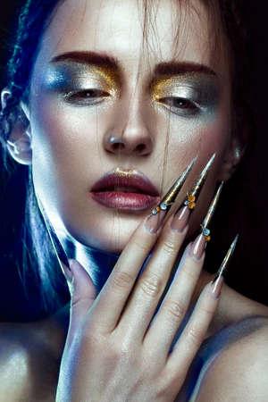 美しい少女創造的な黄金と銀の輝きメイクと長い爪のアート。顔の美しさ。スタジオで撮影した写真
