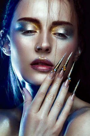 Beautiful girl with creative golden and silver glitter make-up and long nails art. The beauty of the face. Photos shot in studio