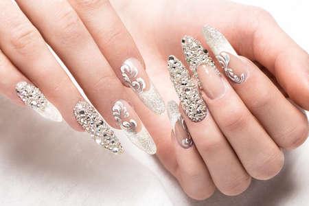 모조 다이아몬드가있는 부드러운 색조의 신부를위한 Beautifil 웨딩 매니큐어. 네일 디자인. 닫다.