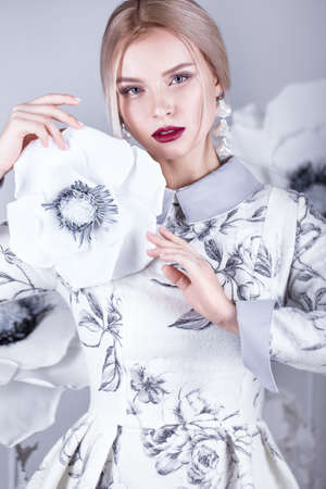 winter photos: Beautiful girl with vintage make-up and hairstyle in a warm winter woolen dress. decoration of flowers. The beauty of the face. Photos shot in studio