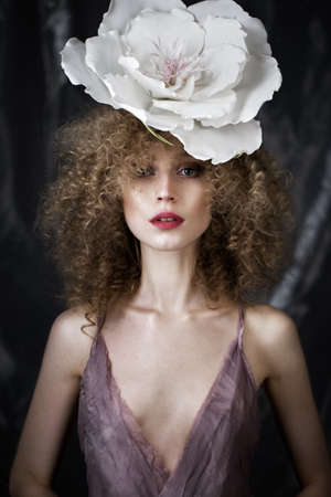Beautiful girl with curly hair in lingerie with large flower. The beauty of the face. Photos shot in studio