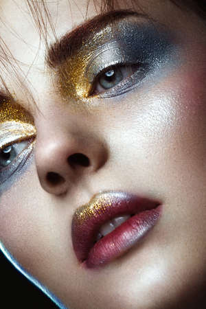 Beautiful girl with creative golden and silver glitter make-up. The beauty of the face. Photos shot in studio