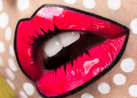 Photo of young woman with professional comic pop art make-up. Creative beauty style. Photos shot in studio. Close up lips