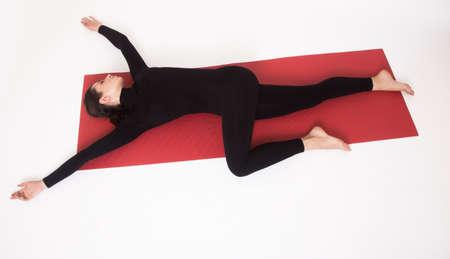 ardha: Beautiful athletic girl in a black suit doing yoga. Ardha Parivritta Nakrasana . Isolated on white background.