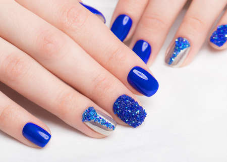 Beautifil blue manicure with rhinestone.. Nail Design. Close-up.