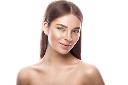 Beautiful young girl with a light natural make-up and perfect skin. Beauty face. Picture taken in the studio on a white background.