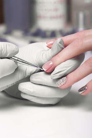 Closeup finger nail care by manicure specialist in beauty salon. Manicurist paints nails with nail polish