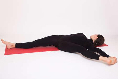 ashtanga: Beautiful athletic girl in black suit doing yoga asanas. Isolated on white background Stock Photo
