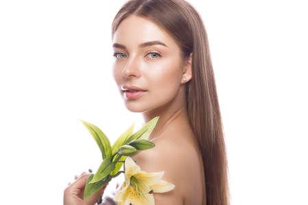 光の自然なメイクと彼女は手に花を持つ完璧な肌の美しい少女。美容顔。白い背景のスタジオでの撮影。