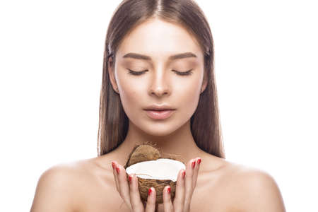 Beautiful young girl with a light natural make-up and perfect skin with coconut in her hand. Beauty face. Picture taken in the studio on a white background. 스톡 콘텐츠
