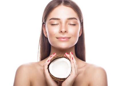 光の自然なメイクと彼女の手でココナッツと完璧な肌の美しい少女。美容顔。白い背景のスタジオでの撮影。