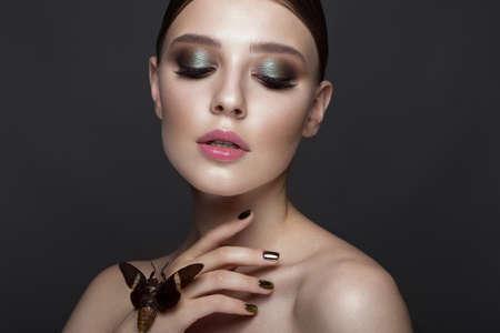 cigarra: Retrato de muchacha hermosa con maquillaje colorido y cigarra. Cara de belleza Foto tomada en el estudio.