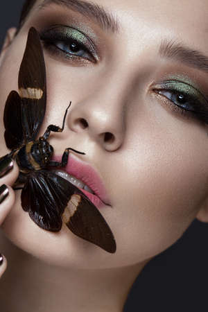 gloss: Portrait of beautiful girl with colorful make-up and cicada. Beauty face. Photo taken in the studio.
