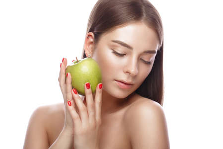 Beautiful young girl with a light natural make-up and perfect skin with apple in her hand.