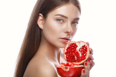Beautiful young girl with a light natural make-up and perfect skin with pomegranate in her hand. Beauty face. Picture taken in the studio on a white background. Stockfoto