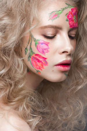 Beautiful blond girl with tresses and a floral pattern on the face. Beauty flowers. Portrait shot in studio Stock Photo