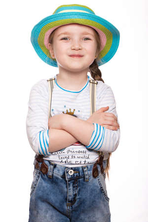 A little girl in a summer Panama, denim overalls. Photo taken in the studio.