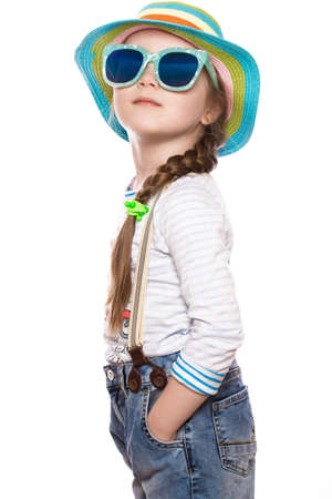 A little girl in a summer panama, denim overalls and sunglasses. Photo taken in the studio.