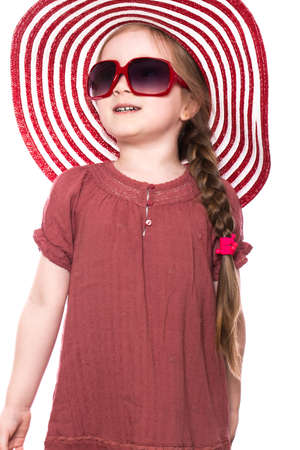 Little girl in summer panama hat, dress and sunglasses. Photo taken in the studio.