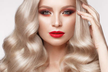 Beautiful blonde in a Hollywood manner with curls, natural makeup and red lips.. Beauty face and hair. Picture taken in the studio Foto de archivo