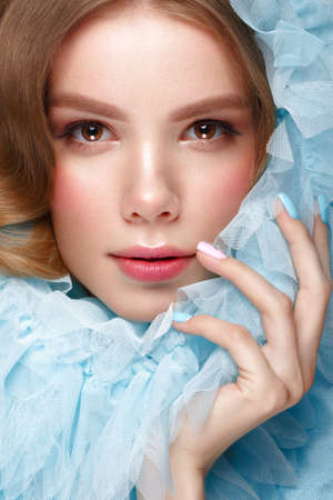 Beautiful girl with light make-up and gentle manicure in blue clothes. Beauty face. Design nails. Photo taken in studio on pink background 写真素材