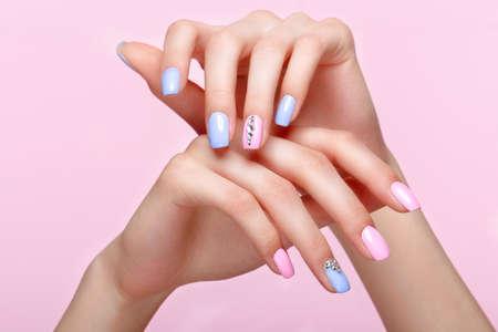 Piękny różowy i niebieski manicure z kryształkami na kobiecej dłoni. Zbliżenie. Zdjęcie zrobione w studio