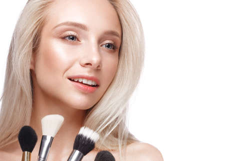 Beautiful young girl with a light natural make-up,brushes for cosmetics and nude manicure. Beauty face. Picture taken in the studio on a white background. Stockfoto
