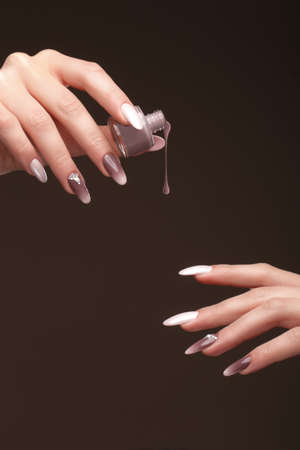 Beautiful classic manicure on female hand with nail polish. Close-up. Picture taken in the studio