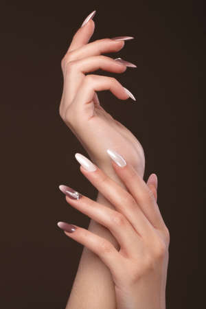 Beautiful classic manicure with crystals on female hand. Close-up. Picture taken in the studio