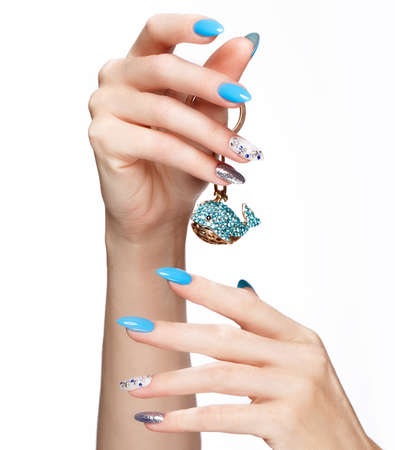 Beautiful summer blue manicure with crystals on female hand. Close-up. Picture taken in the studio