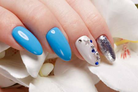Beautiful summer blue manicure on female hand with flowers. Close-up. Picture taken in the studio Standard-Bild