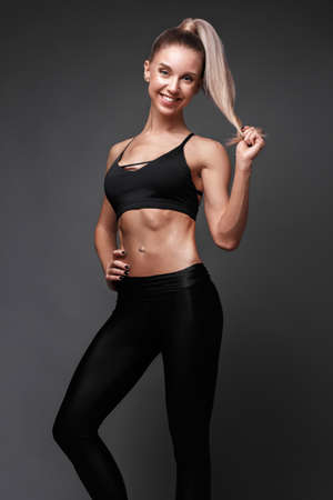 Sports girl with pumped muscles in a tracksuit, leading a healthy lifestyle and posing in the studio. Beauty body. 写真素材