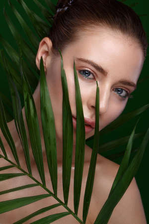 Beautiful fresh girl with cosmetic cream on the face, natural make-up and green leaves. Beauty face. Photo taken in the studio. Stok Fotoğraf