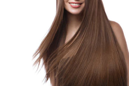 Beautiful brown-haired girl in move with a perfectly smooth hair, and classic make-up. Beauty face and hair. Picture taken in the studio on a white background.