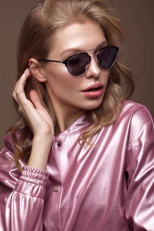 Beautiful girl in stylish pink clothes with sunglasses and sexy lips. Beauty face. Photo taken in the studio