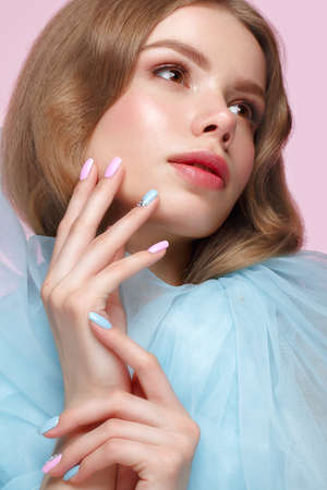 Beautiful girl with light make-up and gentle manicure in blue clothes. Beauty face. Design nails. Photo taken in studio on pink background Standard-Bild - 116071853