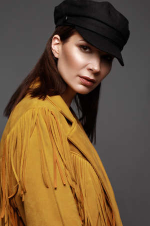 Beautiful girl with a classic make-up and a hairstyle in a fashionable designer jacket and cap, posing in the studio. Beauty face