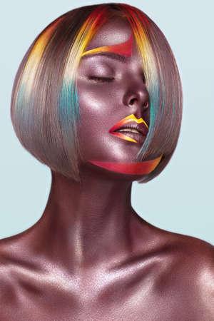 Piękna dziewczyna z wielokolorowymi włosami i kreatywnym makijażem i fryzurą. Piękna twarz. Zdjęcie zrobione w studio
