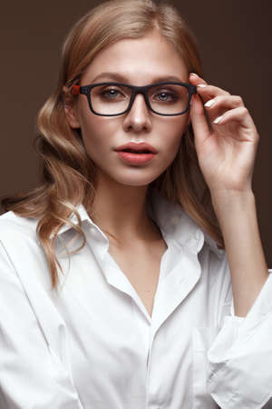 Beautiful girl in stylish clothes with glasses for vision and red sexy lips. Beauty face. Photo taken in the studio Reklamní fotografie